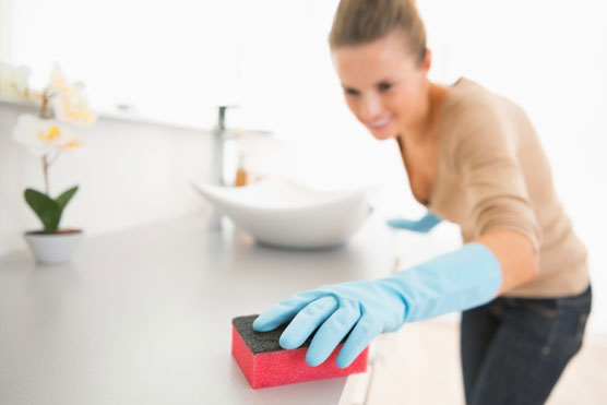 Smiling Woman wearing rubber gloves cleaning a counter-top | Pink Shoe Cleaning Crew | House Cleaning in Greater Omaha