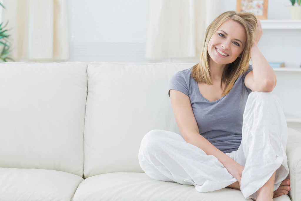 Woman relaxing with hand in hair sitting on a sofa   Pink Shoe Cleaning Crew   House Cleaning Omaha
