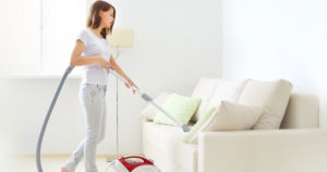 Woman spring cleaning a white sofa | Pink Shoe Cleaning Crew | House Cleaning Omaha