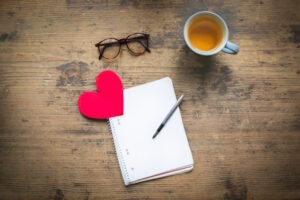 Valentines Day | note pad, heart, pair od glasses and a cup of tea on a table
