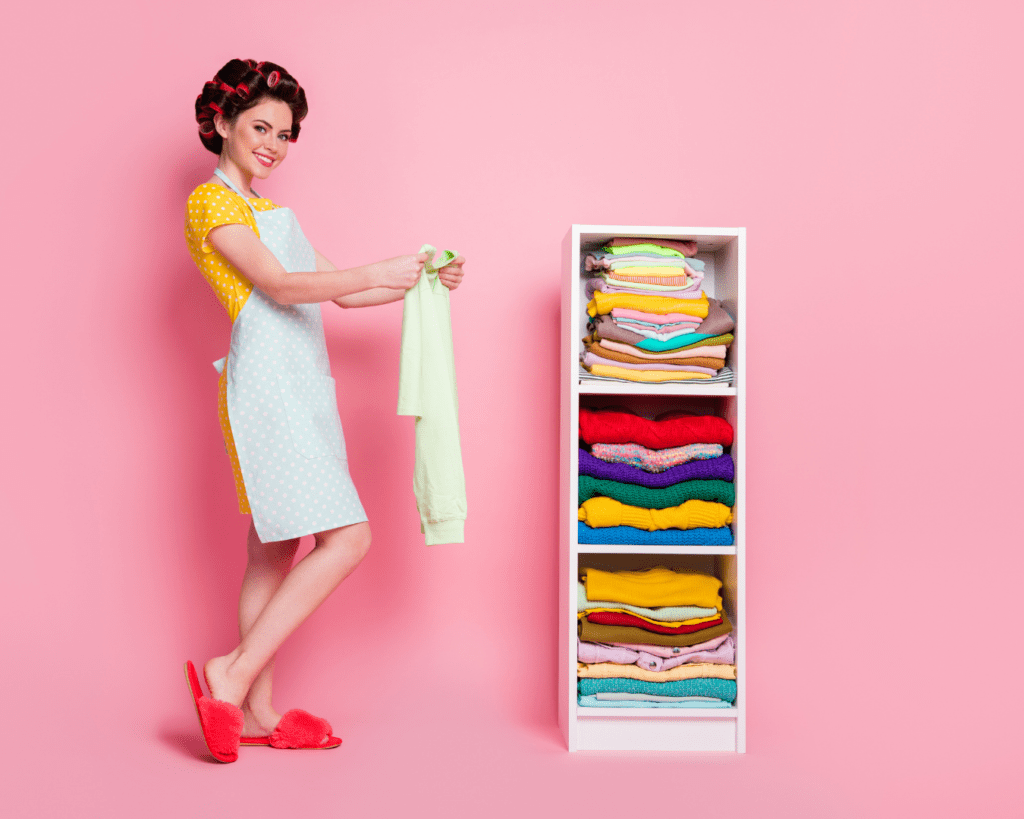Woman with hair in rollers and wearing and apron folding clothes | Spring Cleaning
